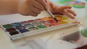 Een kind met een borstel aan verf selecteert de kleur van de verf Reeks waterverfverven van verschillende kleuren stock video