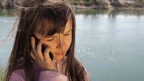 Een kind met een mobiele telefoon door de rivier Het meisje spreekt op de telefoon in de verse lucht Een de lente zonnige dag stock video