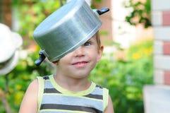 Een kind met een steelpan op zijn hoofd kind met een steelpan Het gelukkige kind stelt tevreden Een kind in een steelpanhoed Royalty-vrije Stock Foto's