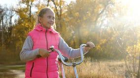 Een kind met een Fiets loopt in het Park in de herfst in de warme zon Een jong meisje is op de weg en rolt de fiets stock videobeelden
