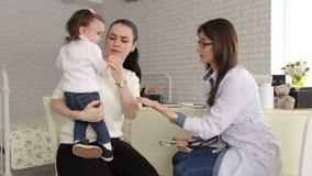 Een kind met haar moeder bij een artsen` s benoeming stock video