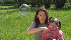 Een kind met haar moeder speelt met zeepbels Een gelukkige familie in de wildernis Het mamma en de dochter blazen bellen stock videobeelden