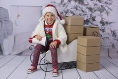 Een kind met Kerstmis stelt en Kerstboom voor stock foto