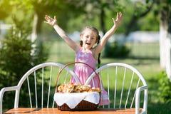 Een kind met een mand brood op een bank Stock Afbeeldingen