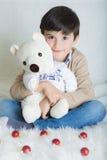 Een kind met zijn stuk speelgoed in Kerstmis Royalty-vrije Stock Foto's