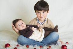 Een kind met zijn zuster in Kerstmis Stock Afbeeldingen