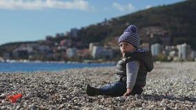 Een kind op het strand kruipt op kiezelstenen stock videobeelden