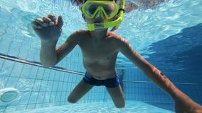 Een kind probeert om het dragen van een het duiken masker te zwemmen stock videobeelden