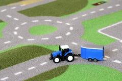 Een kind` s blauwe stuk speelgoed tractor op een tapijt van de wegmat Stock Foto's