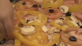 Een kind` s hand zet een bovenste laagje op eigengemaakte pizza stock footage