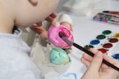 Een kind schildert eieren met een borstel Schilder de eieren voor Pasen stock foto