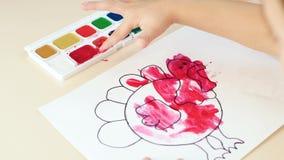 Een kind schildert een vingerbeelden, gebruikend verf, close-up stock videobeelden