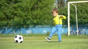 Een kind schopt een voetbalbal op een voetbalgebied in langzame motie algemeen plan stock footage