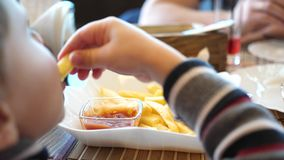 Een kind in een snel voedselkoffie die gebraden aardappels in een plaat eten Dichte omhooggaand van de hand Plakken van aardappel stock videobeelden