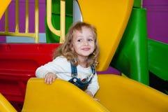 Een kind speelt bij een speelplaats in een winkelcentrum Stock Foto's