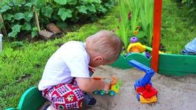 Een kind speelt in de zandbak met de auto stock footage