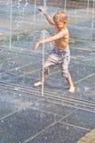 Een kind speelt in een fontein Royalty-vrije Stock Foto