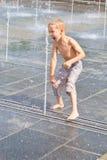 Een kind speelt in een fontein Royalty-vrije Stock Afbeeldingen