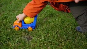 Een kind speelt met een stuk speelgoed auto op het gazon stock video