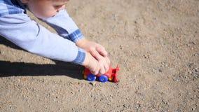Een kind speelt met een stuk speelgoed auto op het zand stock video