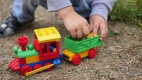 Een kind speelt met een stuk speelgoed trein op het zand Openlucht spelen stock videobeelden