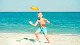 Een kind speelt met een frisbee op het strand stock foto's