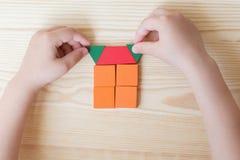 Een kind speelt met gekleurde blokken, creeert een huis op een lichte houten achtergrond royalty-vrije stock foto