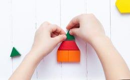 Een kind speelt met gekleurde blokkenconcepten een model op een lichte houten achtergrond Huis royalty-vrije stock fotografie