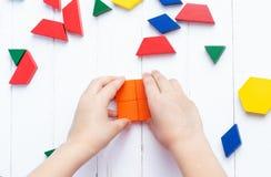 Een kind speelt met gekleurde blokkenconcepten een model op een lichte houten achtergrond Huis royalty-vrije stock foto