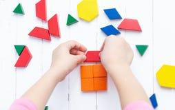 Een kind speelt met gekleurde blokkenconcepten een model op een lichte houten achtergrond Huis stock foto's