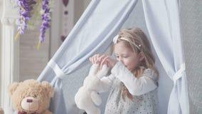 Een kind speelt met speelgoed, die met hen spreken en omhelst een zacht stuk speelgoed stock footage