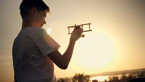 Een kind speelt met een stuk speelgoed vliegtuig bij zonsondergang Silhouet van een jongen die een stuk speelgoed, hand houden di stock footage