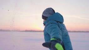 Een kind speelt in openlucht in de winter, in werking stelt, werpt sneeuw tot de bovenkant Mooie Zonsondergang Actieve openluchts stock footage