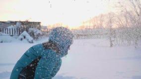Een kind speelt in openlucht in de winter, werpt sneeuw tot de bovenkant Actieve openluchtsporten Zonsondergang stock footage