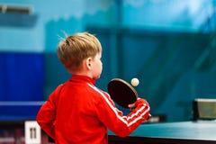 Een kind speelt pingpong in de gymnastiek Stock Foto