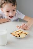 Een kind steelt van een plaat van vers gebakken eigengemaakte koekjes stock foto