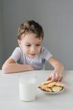 Een kind steelt van een plaat van vers gebakken eigengemaakte koekjes stock afbeeldingen