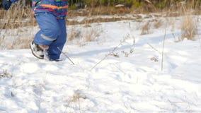 Een kind stelt pret op verse sneeuw in werking In het beeld kan slechts de benen in laarzen worden gezien stock footage