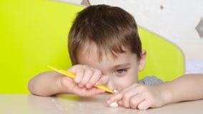 Een kind van peuterleeftijd beeldhouwt een cijfer van plasticine terwijl het zitten bij een lijst Onderwijs, creativiteit en kind stock videobeelden