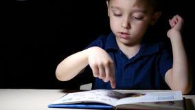 Een kind zit bij nacht bij een lijst die door een lamp wordt aangestoken, leest een boek, richt zijn vinger op de tekeningen in h stock videobeelden