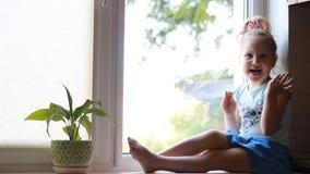 Een kind zit op een venstervensterbank en kijkt uit het venster stock footage