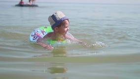 Een kind zwemt op een opblaasbare cirkel in het overzees Gelukkige kinderjaren Positieve emoties stock videobeelden