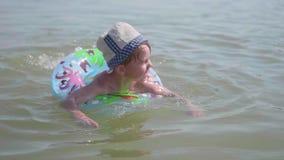 Een kind zwemt op een opblaasbare cirkel in het overzees Gelukkige kinderjaren Positieve emoties stock footage