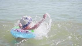 Een kind zwemt op een opblaasbare cirkel in het overzees Gelukkige kinderjaren Positieve emoties stock video