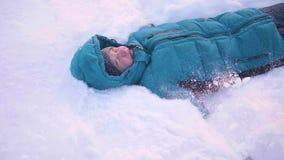 Een kinddaling van de sneeuw in slowmotion Sneeuwonweer Sporten in openlucht Actieve levensstijl stock videobeelden