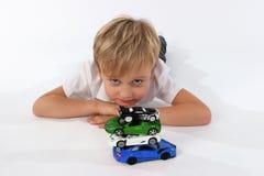 Een kindjongen die met autospeelgoed spelen stock foto