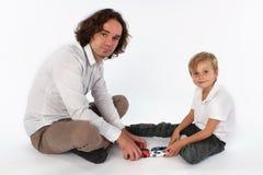 Een kindjongen die met speelgoed met zijn papa spelen stock foto