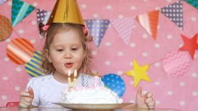 Een kindmeisje blaast uit kaarsen op een verjaardagscake en eet het met zijn vinger De baby maakt een wens stock footage