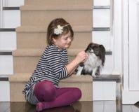 Een kindspel met een hond binnen het huis Stock Foto's