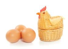 Een kip met drie bruine eieren Stock Foto